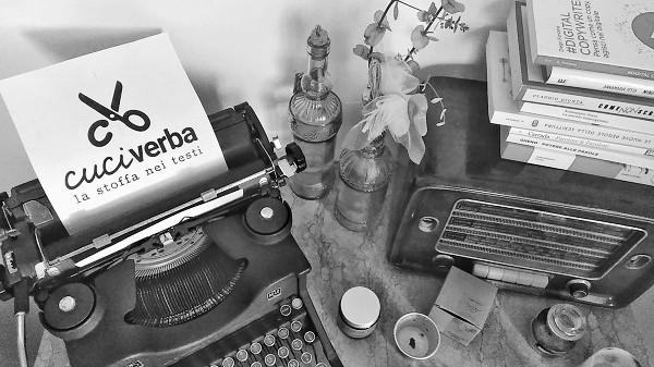 """sopra un tavolo, una macchina per scrivere Olivetti degli anni 40 e un foglio con la scritta """"Cuciverba, la stoffa nei testi"""" e l'icona di un paio di forbici. Sul tavolo anche una radio degli anni 60, delle candele e libri a tema copywriting."""