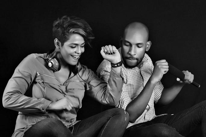 una donna e un uomo, giovani afroamericani, sono seduti e si muovono come per ballare. Lei, ha le cuffie al collo.
