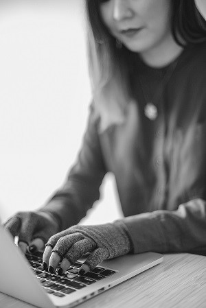 Una donna asiatica disabile scrive con il laptop e indossa i guanti di compressione. A fuoco sono le mani e la tastiera.
