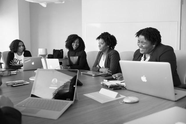 donne imprenditrici nere al tavolo per una riunione, sorridenti, ognuna davanti al proprio laptop