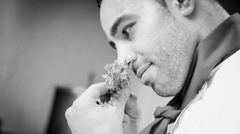 uno chef annusa una pianta aromatica
