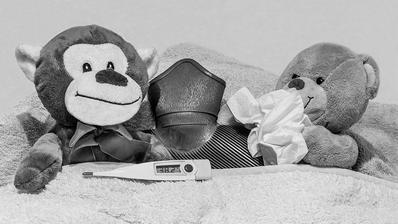 una scimmietta e un orsacchiotto peluche sono a letto malati con termometro, fazzoletto e borsa dell'acqua calda