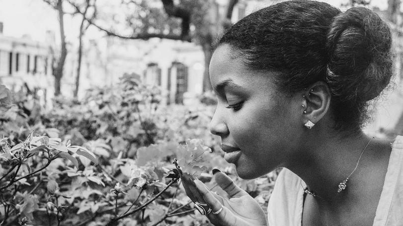 una ragazza nera annusa con l'olfatto il profumo di un fiore