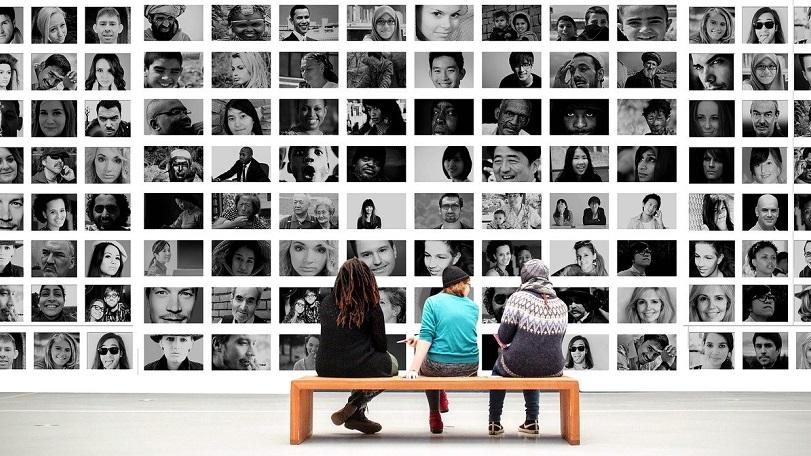 tre persone sono sedute su una panca in un museo e guardano un'opera composta da moltissime foto in bianco e nero di persone giovani, anziane, donne, uomini, nere, bianche, asiatiche. il linguaggio inclusivo rappresenta tutte le comunità meno rappresentate