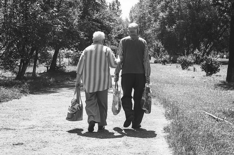 due persone anziane in una foto in bianco e nero camminano in un parco e hanno in mano buste della spesa