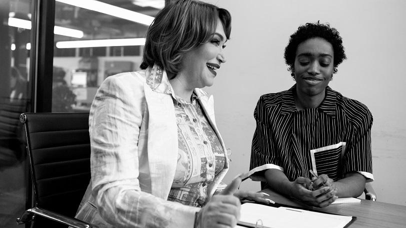 Due persone che lavorano insieme: una donna transgender e una persona non binaria, sorridono in un meeting di lavoro. La foto è in bianco e nero