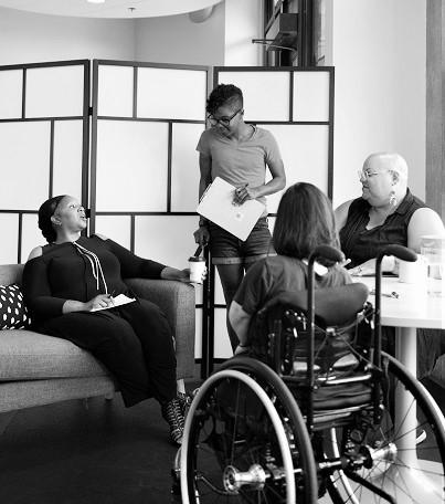 Quattro persone con disabilità si riuniscono intorno a un tavolo durante una riunione. Una donna nera è seduta su un divano, gesticola e parla mentre gli altri tre individui (una persona dell'Asia meridionale seduta su una sedia a rotelle, una persona nera non binaria seduta su una sedia e una persona nera non binaria in piedi con una lavagna per appunti e un bastone) la guardano e la ascoltano. La foto è in bianco e nero.